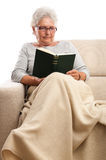 Old woman at home reading book Stock Photography