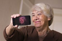 Old woman at home smiling. To selfie Stock Photo