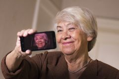 Old woman at home. Taking selfie Stock Image