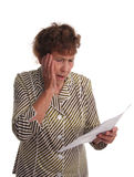 Old woman with horror looks at a sheet of paper Stock Photography