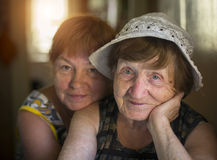 Old woman and hugging her daughter in the background, in the house. Stock Photo