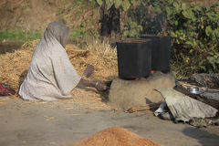 Old woman husking paddy. She is boiling paddy in a open place Royalty Free Stock Photos