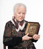 Old woman with icon stock image
