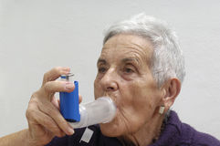 Old woman with an inhaler. An old woman with an inhaler Stock Image