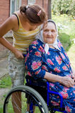Old woman in an invalid armchair Stock Image