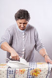 Old woman ironing clothes Royalty Free Stock Photo