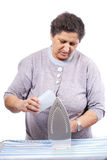 Old woman ironing clothes Royalty Free Stock Image