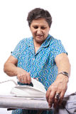 Old woman ironing clothes Stock Photos