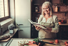 Old woman in kitchen Royalty Free Stock Photography