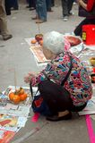Old woman kneeling seeking blessings. An old woman at Wong Tai Sin Temple in Hong Kong on the first day of the Chinese New Year making an offering and seeking Royalty Free Stock Photo