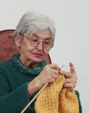 Old woman knitting. Portrait of an old woman knitting,against a gray background Stock Photography