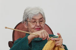 Old woman knitting. Portrait of an old woman knitting,against a gray background Royalty Free Stock Photo