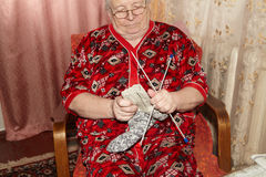 Old woman and knitting clothes Stock Photos