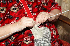 Old woman and knitting clothes Royalty Free Stock Photography