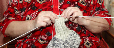 Old woman and knitting clothes Stock Images