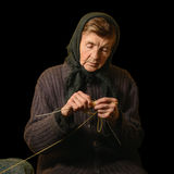 Old woman knitting. Low key photograph on black background. Royalty Free Stock Image