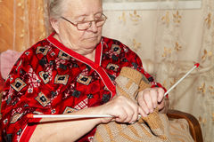 Old woman and knitting sweater Stock Images