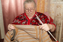 Old woman and knitting sweater Royalty Free Stock Images