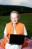 Old woman with laptop. On a meadow Royalty Free Stock Photography