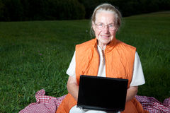 Old woman with laptop. On a meadow Royalty Free Stock Photos