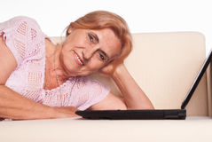 Old woman with laptop Stock Images
