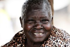An old woman laughing with teeth. An old woman, sister, mother, grandmother, with a big grin showing teeth in Gulu Uganda royalty free stock photo