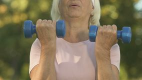 Old woman lifting dumbbells, workout effort, outside training, body care, health. Stock footage stock footage