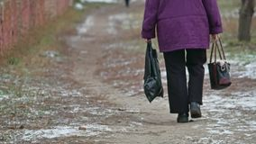 Old woman is limping down the street, bears a bag and a package of late autumn outdoor. Old woman is limping down the street, bears a bag and package of late stock video