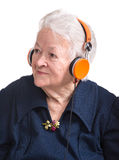 Old woman listening to music in headphones Royalty Free Stock Image