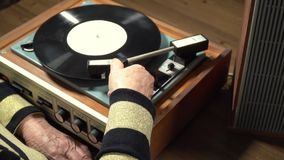 Old woman listening vinyl record on player stock footage