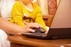 Old woman with laptop. Senior grandmother indoors with notebook. Web surfing and shopping on the Internet. Social networks. Diffic. Old woman and little child royalty free stock image