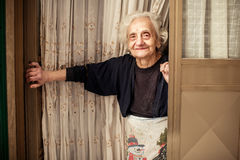 Old woman looking out of the door Stock Photos