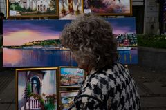 Old Woman Looking at Paintings royalty free stock images