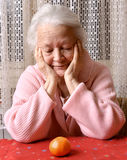 Old woman looking at tangerine. At home Royalty Free Stock Photography