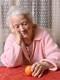 Old woman looking at tangerine. At home Royalty Free Stock Images