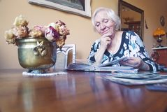 Old woman is watching an album with old photos. stock photography