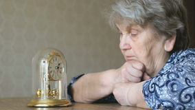 Old woman looks at the table clock with pendulum stock video footage