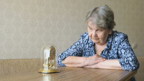 Old woman looks at the table clock with pendulum stock video