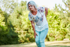 Old woman with lumbago pain. While walking in the nature Stock Photo