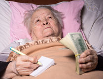 Old woman lying in bed Stock Images