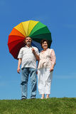 Old woman and man holding umbrella Stock Photos
