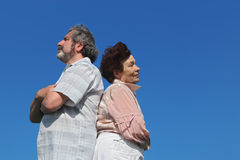 Old woman and man standing back to back Stock Images