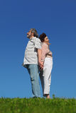 Old woman and man standing back to back Royalty Free Stock Photo