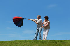 Old woman and man standing on lawn with umbrella. Old woman and man standing on summer lawn with multicolored umbrella, wind evert it Stock Photo