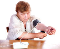 The old woman measures arterial pressure upon. A white background stock photos
