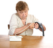 The old woman measures arterial pressure upon. A white background royalty free stock image