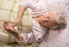 Old woman measures arterial pressure Stock Photos