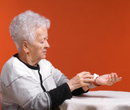 Old woman measures arterial pressure. On an orange background stock photography