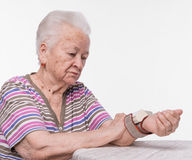 Old woman measures arterial pressure. On a white background royalty free stock photos