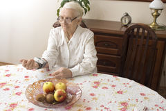 The old woman measures the pressure apparatus wrist. The old woman measures arterial pressure while sitting in the living room at the table Stock Images